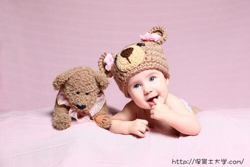 クマのニット帽をかぶって喜ぶ赤ちゃん