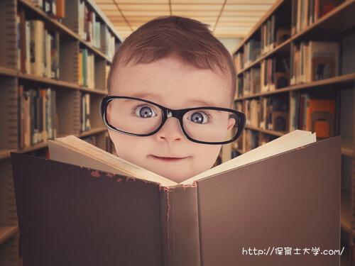 メガネをかけて読書する男の子。保育大学の選び方