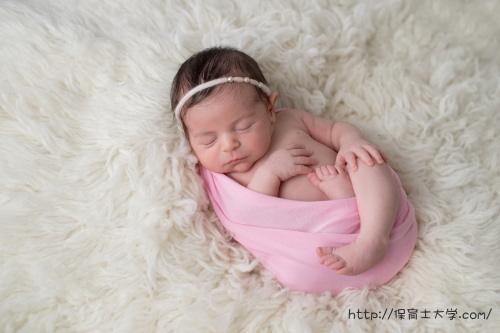 ピンクのおくるみに包まれて安心して眠る子供