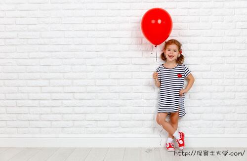赤い風船をもった保育園児3歳