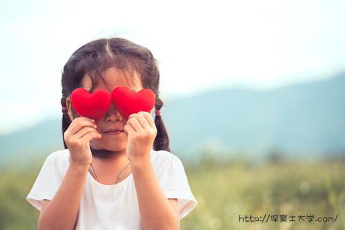 ハート型のおもちゃで目を隠す少女