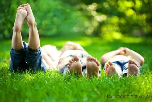 保育園のお庭で寝転んで遊ぶ園児